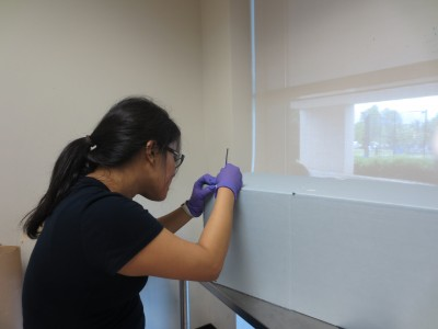 With guidance from a Washington Conservation Guild volunteer, a Morgan State student constructs a box to house a dress.