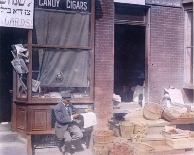 Hand-tinted lantern slide of a man reading the paper in front of a store on East Lombard Street. Courtesy of the Ross J. Kelbaugh Collection. 1988.226.004a