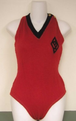 Bathing suit made of knitted wool, and matching black and red cotton stockings with the red woven into a lacey design down the front.ca. 1916-1920. Red with black v-neck, and black felt appliqued pierced design over left chest area. Two buttons on left shoulder of undetermined material. Bathing suit belonged to donor's mother, Esther Selma Benjamin Bernstein, c. 1916-1920 (1991.188.1)