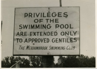 "Black and white photograph of a sign outside of the Meadowbrook Swimming Club. The sign reads: ""Privileges of the Swimming Pool Are Extended Only to Approved Gentiles  The Meadowbrook Swimming Club."" The photograph shows the walkway up to the pool as well as what is presumably the clubhouse in the background. (1995.201.001)"