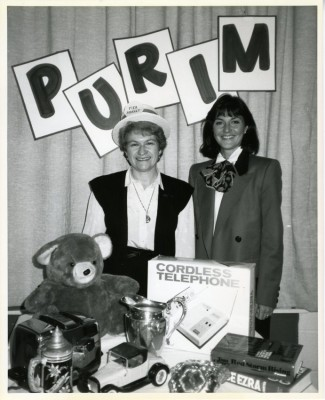 Flea market table at the 1987 Purim Carnival.  Pictured are Shelby Gilden, JCC Chairman, and Ms. Hirsh. Gift of the Jewish Community Center of Greater Baltimore, 2006.13.307.
