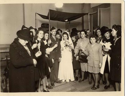 Gela Baser and Fred Perchal at their wedding with guests in Brussels, Belgium, November 28, 1945.  Courtesy of Rabbi Manuel Poliakoff. 1996.113.7.