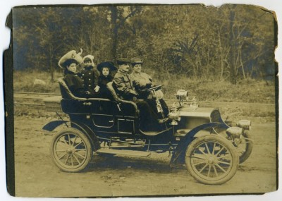"Greenfelder family portrait in an automobile ""the Premier Car"" at Park Entrance of Druid Hill Park, November 8, 1905.  R-L: Jeannette Greensfelder, Lewis Greensfelder and Ruth Greensfelder (Frank) in black hat, Elmer Greensfelder in rabbit -ear hat. Woman in white hat is unidentified. Courtesy of Mrs. Susan S. Merrill. 2010.60.11."