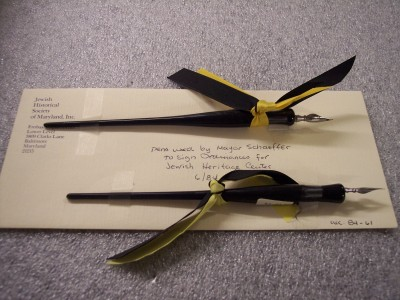 Pen used by Mayor William Donald Schaefer to sign ordinances for the Jewish Heritage Center, with yellow and black ribbon attached. Pens are attached to an envelope. Courtesy of William Donald Schaefer. 1984.61.1.