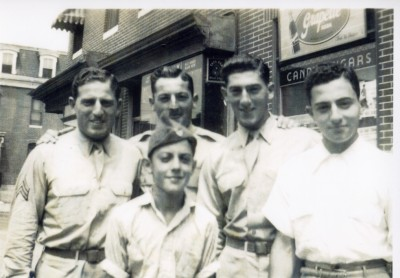 Black and white photograph of the Matz brothers in their WWII service uniforms standing at the corner of Patterson Park and Fairmont Avenue (L-R): Herbert (US Army Air Forces) , Wilbur (Army), Lester (Army), Jacob (joined the army the following year) and Charles (in front.)