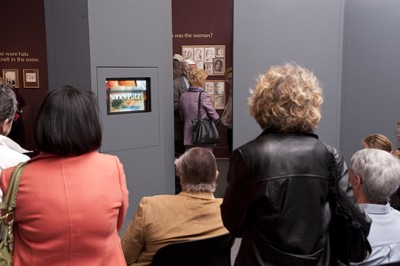 Visitors crowd around the TV cabinet at the opening of Nancy Patz: Her Inward Eye  in April 2010.