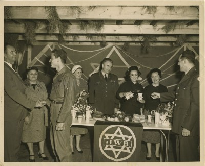 2001.040.017 – This photo from 1959 depicts members of the Ladies of the Holiday Committee of the Baltimore Jewish Welfare Board serving wine and cake in a sukkah to Jewish troops of the Aberdeen Proving Ground.