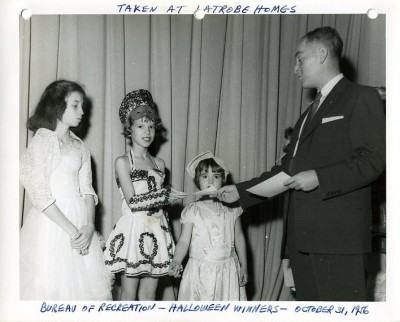 Bureau of Recreation's Halloween Winners, taken at the Latrobe House on October 31, 1956. Jacob Fisher is presenting the awards to the winners.