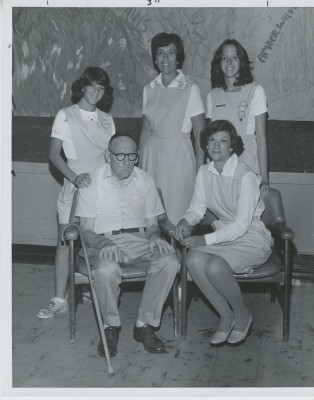 Two other mother-daughter teams are photographed volunteering and spending time with Mr. Bain. The mother-daughter teams from left to right are Gail Feinberg, Mrs. Henry Lesser, Jackie Lesser, and Mrs. Gilbert Feinberg.