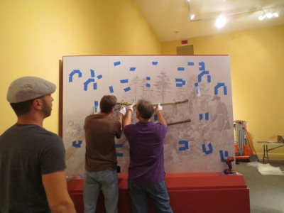 Rather than drilling holes directly into the large graphic, the guys map out the weapons case with blue tape.