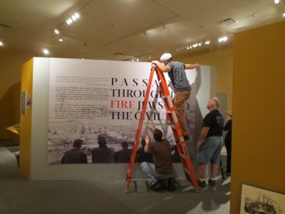 Mounting the dramatic three-part entrance panel really sets the stage for this exhibition.