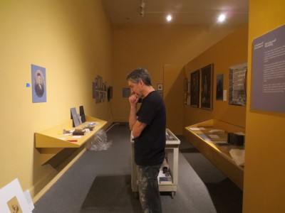 "Paul ponders the spacing on another wall, and wonders if the carefully measured pieces will ""read"" to the public. Believe me, this important step can make or break the continuity of the exhibition story."