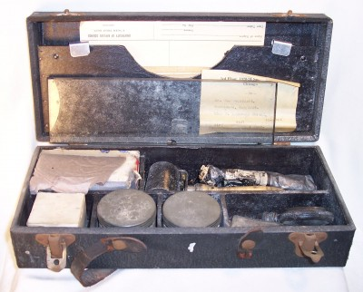 1988.156.005 Fingerprinting set, complete in case. The kit contains: 6 pieces of cardboard of varying sizes; sensitized card in glassine envelope; blank fingerprint form; address label; glass plate; watch case; glass bottle with cork; tube of black ink; ink roller; 2 jars with lids; optical instrument in cardboard box; cotton in cardboard box.  All items were owned by William Weinblatt.