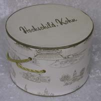 1992.146.003 Small hatbox: Hochschild and Kohn Co., beige colored box with scenes of Baltimore landmarks in gold.