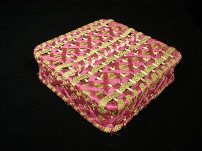 1992.239.005 Sewing box with wood base, wood dowels woven with pink and naural straw plaits, hinged. Marked Huyler's, New York, ca. 1900.