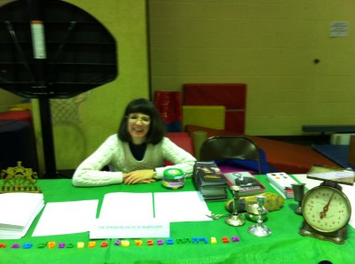Robyn Hughes sits behind the JMM's table at the expo.