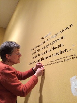 Curator Karen Falk removes wall text in preparation for our next exhibit - Project Mah Jongg!