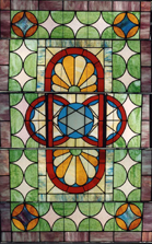 One of two stained glass skylights from the Komar Building, Baltimore. The skylights were removed from the balcony of the old theater and from the main stairwell of the building. The design of each skylight contains a central medallion featuring a Star of David. The lights are made of opalescent and cathedral glass. The theater skylight has a cartouche and fan motif surrounding the central medallion, the other skylight medallion is flanked by stylized floral emblems set in a geometric field; both lights c. 1915. 1993.038.002
