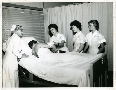 Three Sinai nursing students and their instructor stand around a patient in his hospital bed, June 1960. Accession # 2010.020.316. Courtesy of Nurses Alumnae Association of Sinai Hospital.