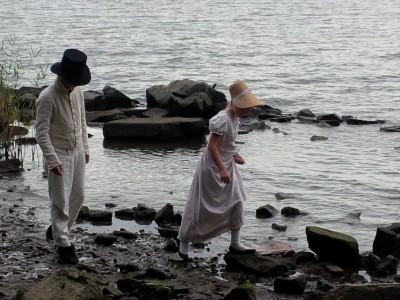 Re-enactors walk along the water's edge.