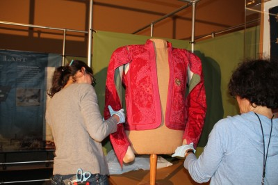 Collections Manager Joanna Church and Assistant Director Deborah Cardin install Mendes' newly conserved jacket.
