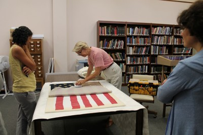 Textile conservator, Michele Pagan, arrived with the flag that Mendes made to hoist up the sail as he traveled on the Nile. Michele has been working for several weeks to fill in the color of the red stripes that have faded and to repair the paper stars that have disintegrated. Here she is gently cleaning the flag before its installation in a special case designed and fabricated by Mark Ward.