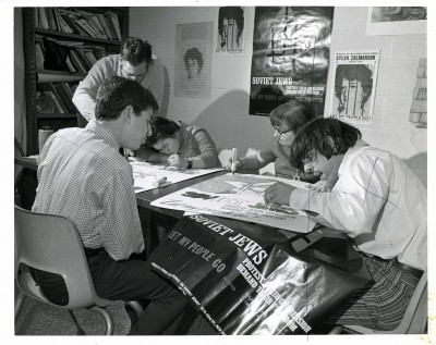"""Soviet Jews protest their oppression demand their freedom let my people go."" A group of young men working on protest posters at the JCC, January 1973. Photo by Sussman Photography, JMM 2006.13.1553."