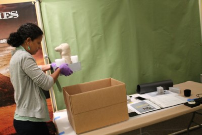 First, Joanna Church, the Collections Manager, and the conservators, moved out the fragile and valuable objects such as Mendes's flag. Pictured here is one of the conservators using nitrile gloves to handle objects.