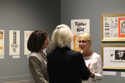 Visitors have a conversation about the film posters in the exhibit.