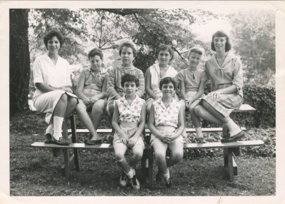 Girls and female counselors sitting on a picnic table. JMM 1993.37.22
