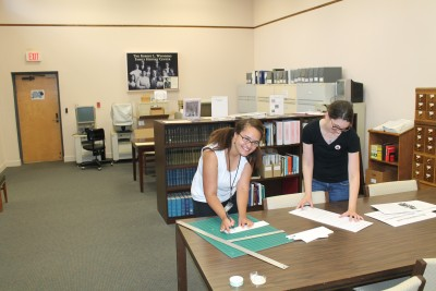 Falicia and Collections Manager Joanna in the library cutting out exhibit text.