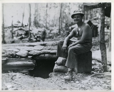 """Technician Fourth Grade Louis Fox, of 3041 Spaulding Ave., Baltimore, MD was photographed recently by his dugout, called the ""Sad Sack's Hole,"" on an advance island base in the South Pacific war theater. Sgt. Fox is one of the few Baltimore men who fought with the 43rd Infantry Division throughout the entire New Georgia campaign, a battle which paved the way for the invasion of Bougainville."" Bureau of Public Relations, War Department, Washington"