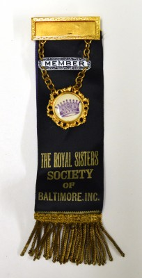 "Satin badge with metal and enamel badges, and metallic fringe. ""Member, The Royal Sisters Society of Baltimore, Inc.""  Gift of Helen Glaser. JMM 1998.114.9a"