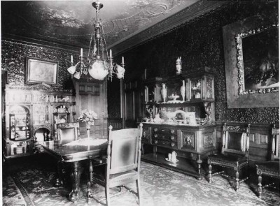 The cabinet (pictured far left) in use in the dining room of the Hutzler home on Eutaw Place. (JMM 1991.024.001a)