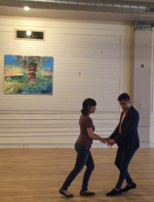 The salsa instructor demonstrates a move with one of my peers.