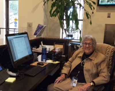 Front desk volunteer Betsey Kahn poses with the new touch screen system!