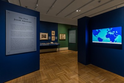 Photo of the entrance to an exhibit, with a text panel on the left and an illuminated world map on the right