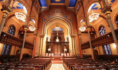 Color photo of the interior of the Central Synagogue building. The room is lit with golden light.