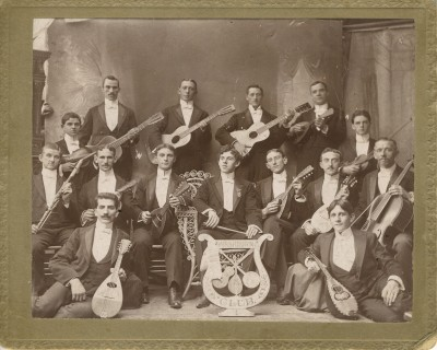 The Washburn Club, circa 1900.  Each member is holding an instrument, primarily strings; their logo, featured in the cardboard cut-out in the center front, consists of a mandolin, guitar, and banjo within a lyre.  Bonus: spot the disembodied hand holding on to the backdrop in the upper left.  Gift of Mr. and Mrs. Morton K. Sugar. JMM 1987.193.2
