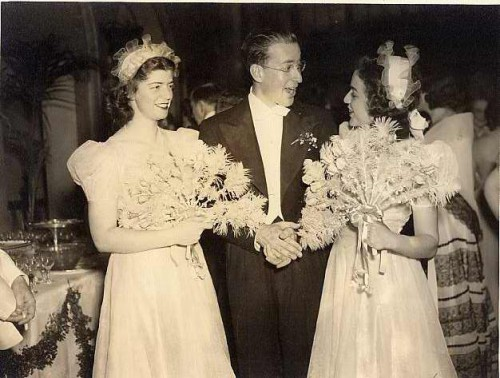 Left to right: Betty Hahn, Richard Lansburgh, and Selma Freedman at the wedding of Sidney Lansburgh, Jr. and Helen Brylawski at the Mayflower Hotel in Washington, D.C., 1940. In your imagination, please color their dresses aquamarine, their fans pink, and their hats beige with aqua ribbons. Gift of Margaret Nomentana. JMM 2004.108.9
