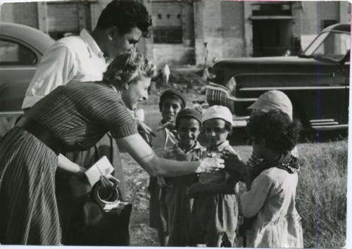 Grace Heller hands out candy to a group of Yemenite Children on an Associated mission, 1954. Her chauffeur Jack Handeh assists. JMM 1995.142.6.5