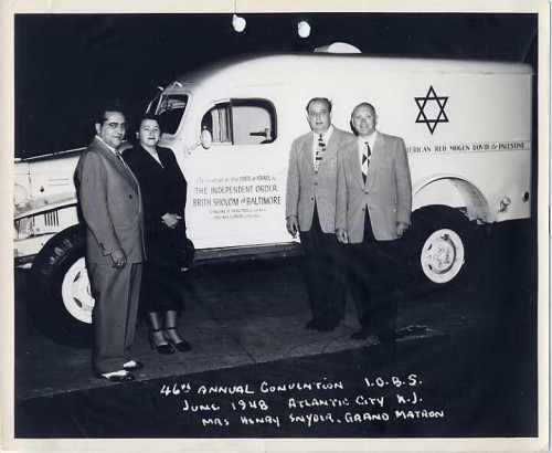 The Independent Order Brith Sholom (IOBS), a fraternal organization formed in 1902 in East Baltimore, was the first fraternal order to buy ambulances for the new state of Israel. It also helped supply money and material for the ship Exodus, helped fund settlement for Yemenite Jewish immigrants, and raised money to build the Brith Sholom of Baltimore Medical Center in Rishon L'Zion. Here, Grand Matron Kay Snyder and three unnamed men stand in front of a truck presented to the new state of Israel during the 46th Annual Convention of IOBS in Atlantic City, June 1948. JMM 1995.209.84.2