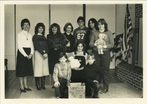 "The National Council of Jewish Women (NCJW), founded in 1893, focuses on women's issues, philanthropy, and community. In 1953 the NCJW began the ""Ship-A-Box"" program, sending toys, books and games to children overseas, especially to Jewish children in the immigrant settlements of Israel. Here Maryland Jewish youth help NCJW Annapolis Section leaders with the ""Ship-A-Box"" project, displaying dolls to be sent to Israel, c. 1985. Pictured are (top L to R): Sue Merrill, Section President Robin Sussman, Donna Berusch, Janice Singerman, George Gordon, Jane Cohen, and Tanya Peskin, (bottom L to R): Wade Berusch, Julie Merrill, and Bessie Gordon. JMM 2001.113.82"