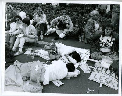 """In this black and white image, a group of people sit near the road, on the curb. Two of the people in the image are laying down on the road, asleep. There is a sign that says """"Choice. Legal"""""""
