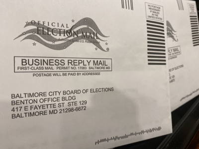 "An image of two envelopes addressed to the Baltimore City Board of Elections. A logo indicates that this is ""Official Election Mail""."