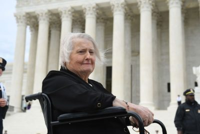 An older white woman sitting in a wheel chair is pictured in front of the US Supreme Court building.