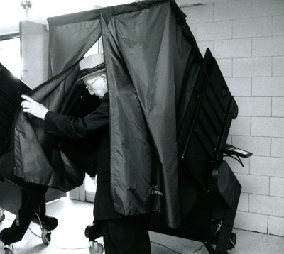 In this black and white image, an older, white man steps out of a polling booth, which has curtains he's pulling aside for privacy.
