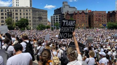 """Int his image there is a crowd of people as far as the eye can see, with large buildings int he background. Most of the people are wearing white. Some are carrying signs, one that says """"TRANS RIGHTS NOW."""""""