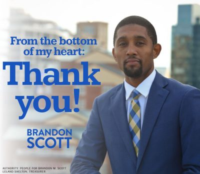 "A picture of Brandon Scott, a black man wearing a suit and tie, standing outside. There are buildings out of focus in the background. The text on the image reads: ""From the bottom of my heart: Thank you! Brandon Scott""."