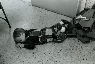 In this black and white photo, a toddler lays asleep on a floor, near a pile of coats.